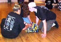 Students huddled around a robot