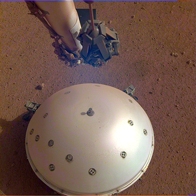 This image, taken March 19, 2019 by a camera on NASA�s Mars InSight lander, shows the rover�s domed Wind and Thermal Shield, which covers its seismometer, the Seismic Experiment for Interior Structure, and the Martian surface in the background.